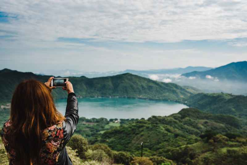 woman taking photo of green covered mountain